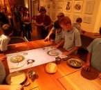 A group of school students look at a selection of props and AVs, including recreated bread and food in bowls. A large screen set into a table shows the arms of convicts eating food.