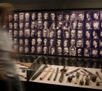 Image of a man moving past a wall covered in early 20th century mugshots. Underneath is a showcase containing weapons.