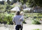 Father carrying son through the kitchen garden.