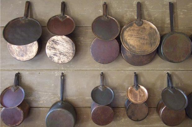 Batterie de cuisine, rows of cooking pans and lids hung on the wall.