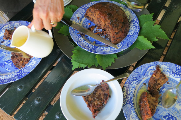 A Christmas plum pudding cut up, slices on plates and half eaten with plum pudding sauce being poured on.