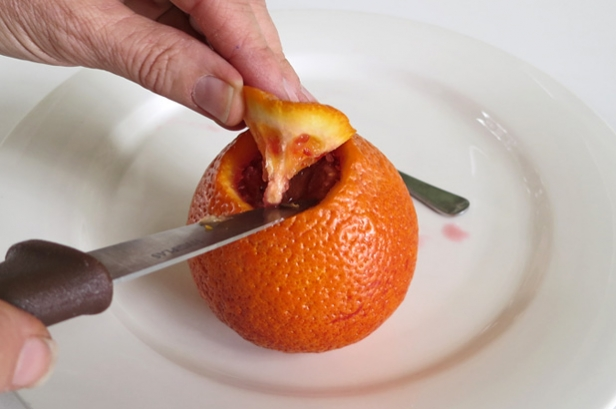 Cutting the top out of an orange.