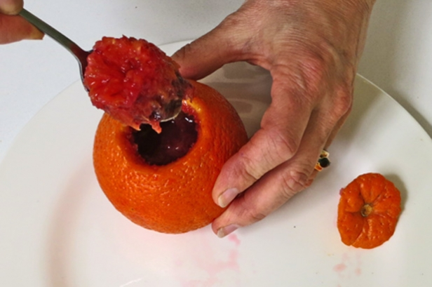 Scooping the flesh from the orange.