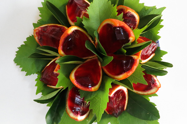 Jelly filled oranges cut into wedges and decorated with grape leaves.