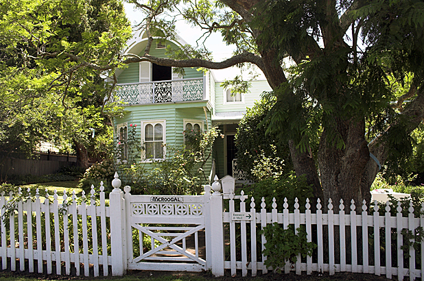 The house seen from the front, behind a white picket fence and gate with Meroogal painted on it.