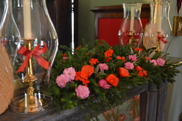 An arrangement of flowers, greenery and candle shades on the chimneypiece at Elizabeth Farm.