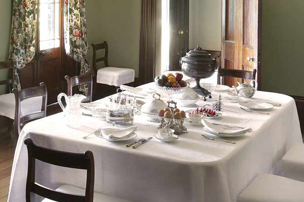 The Elizabeth Farm dining table set for breakfast with eggs, fruit and tea visible on the table.