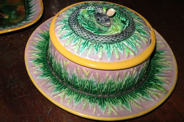 A covered serving dish decorated with a snake and leaves.
