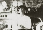 Detail of photograph showing Fred Hughes sitting in the basement kitchen, stove in the background.