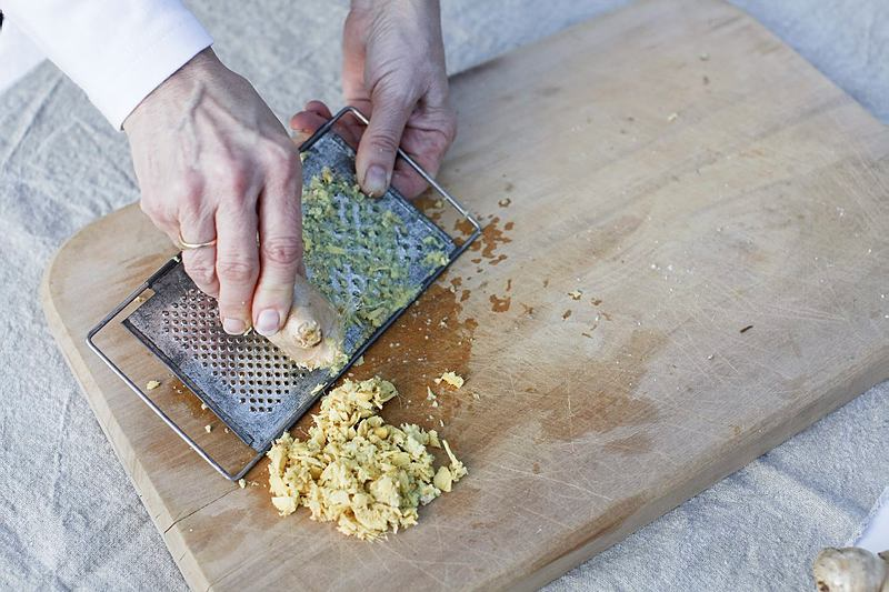 Grating ginger on a wooden board, to make ginger beer.