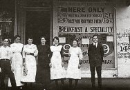 Close up detail of Emmanuel (far right) and staff standing outside his restaurant, c1920s.