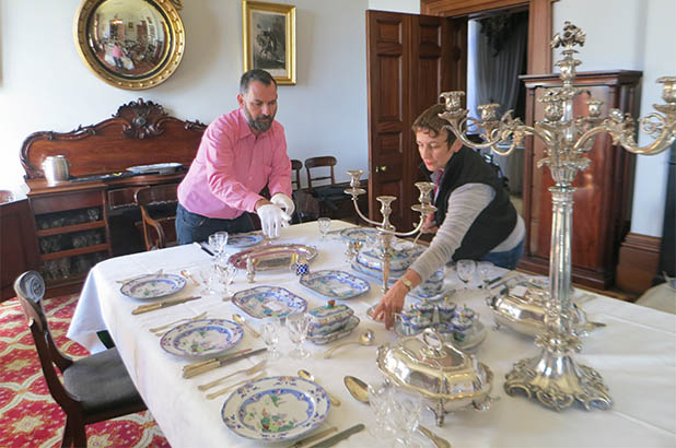 The Cook and the Curator set a table with china and silverware.