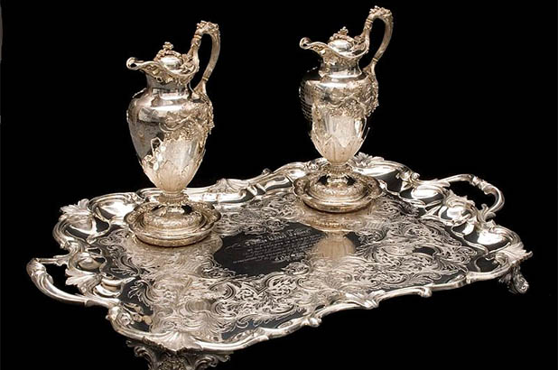Two silver claret jugs, two silver coasters and a silver presentation tray.