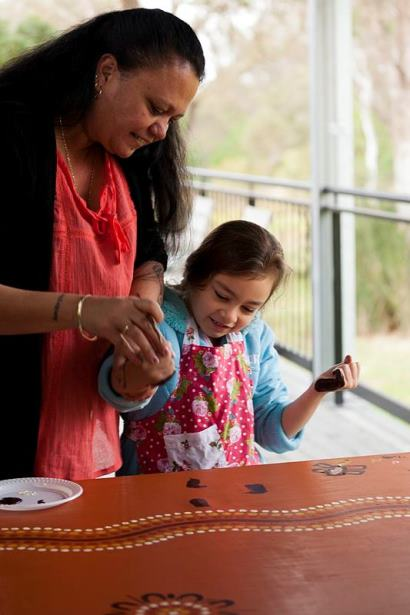 Leanne Watson local Darug woman and chairperson of the Darug Custodians Aboriginal Corporation demonstrates painting techniques to Isabella Redpath