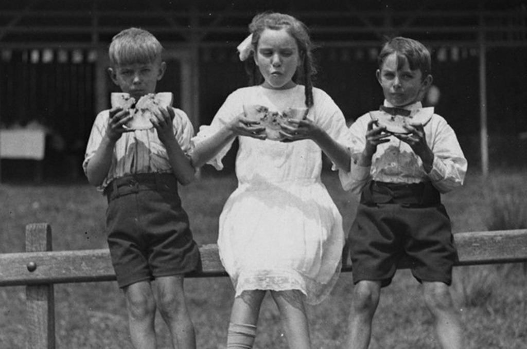 Black and white photograph of three children eating watermelon